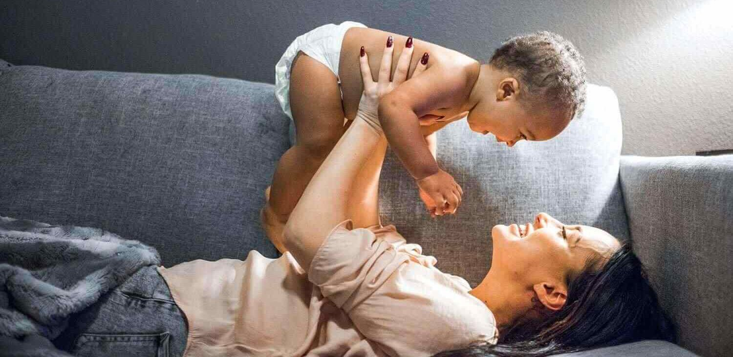 woman on a couch holding baby in the air