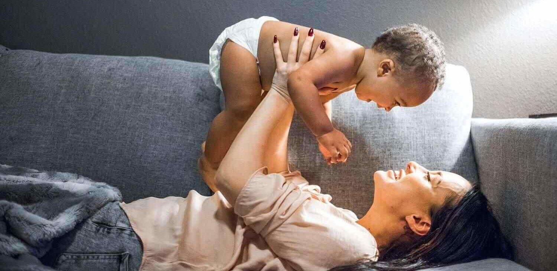 mujer en un sofá sosteniendo un bebé en el aire