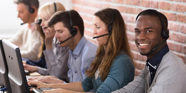 customer service representatives on the computer and speaking on headsets